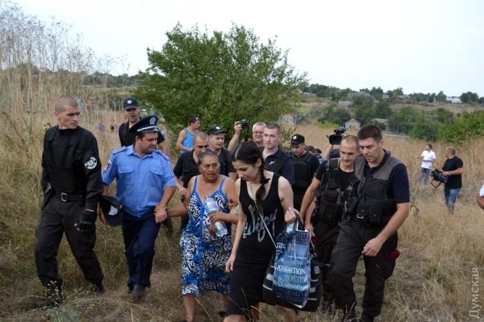 Поліція охороняє їх від натовпу і супроводжує до своєї машини. Фото: Думская.