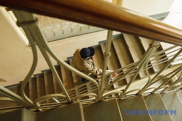Годинникар Василь Дуфинець піднімається сходами до головного годинника на Мукачівській міській ратуші