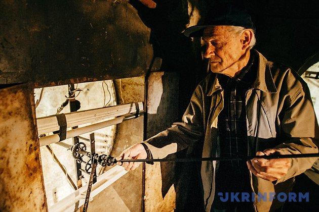 Годинникар Василь Дуфинець стоїть біля циферблату