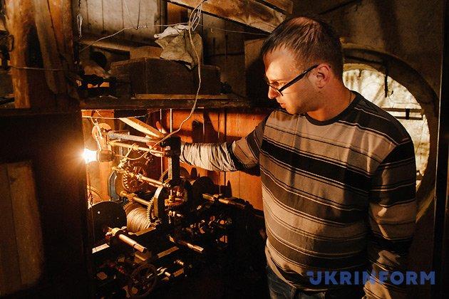 Годинникар Іван Онисько стоїть біля механізму годинника