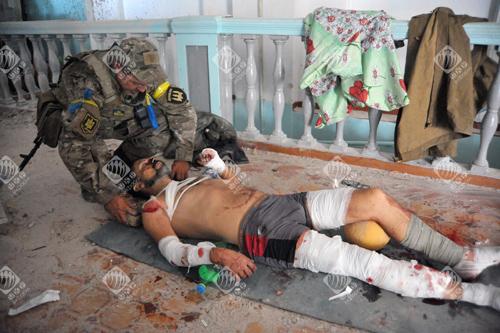 Український військовослужбовець допомагає пораненому бійцю у спортзалі Іловайська