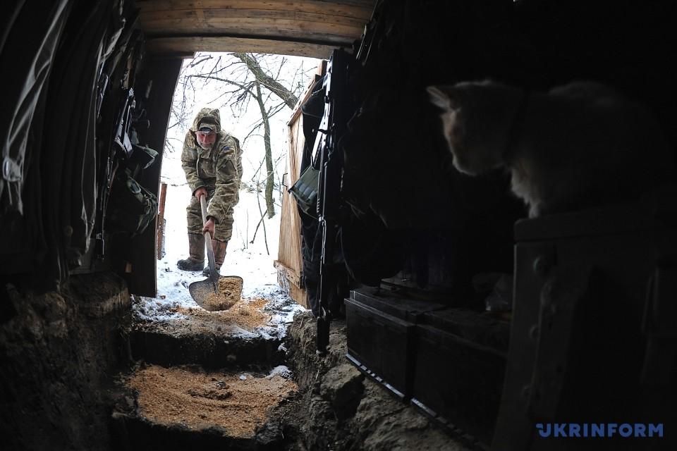 Боєць АТО посипає тирсою сходи на вході до бліндажа, Донецька область, 9 січня 2016 року. Фото: Олена Худякова/Укрінформ