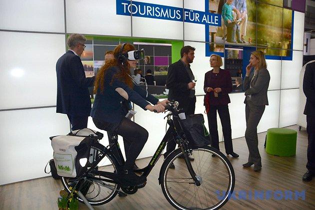 Женщина на велосипеде во время туристической выставки