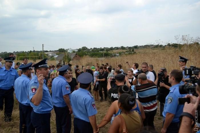 Полиция охраняет их от толпы и сопровождает к своей машине