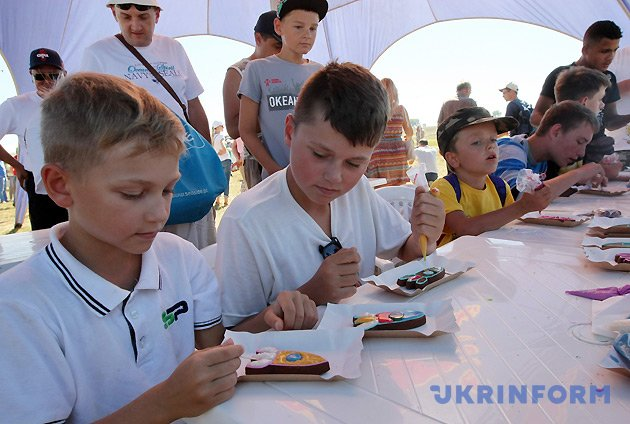 Діти наносять кольоровий крем на печиво у вигляді ракет