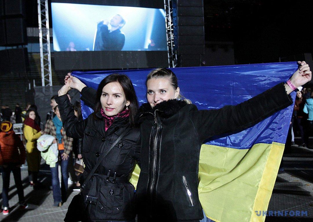 Девушки держат в руках государственный флаг Украины во время концерта группы