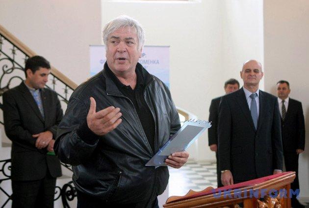 Народний артист України Анатолій Хостікоєв вручає відзнаку представнику міста Диканьки