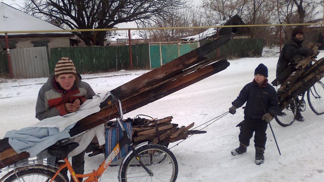 Сім'я в Трьхізбенці везе на дрова колоди з розбитого обстрілами будинку (грудень 2014р.)