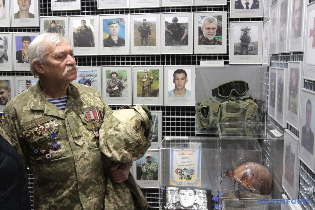 Ветеран АТО роздивляється фотографії загиблих українських військовослужбовців та їхні особисті речі у