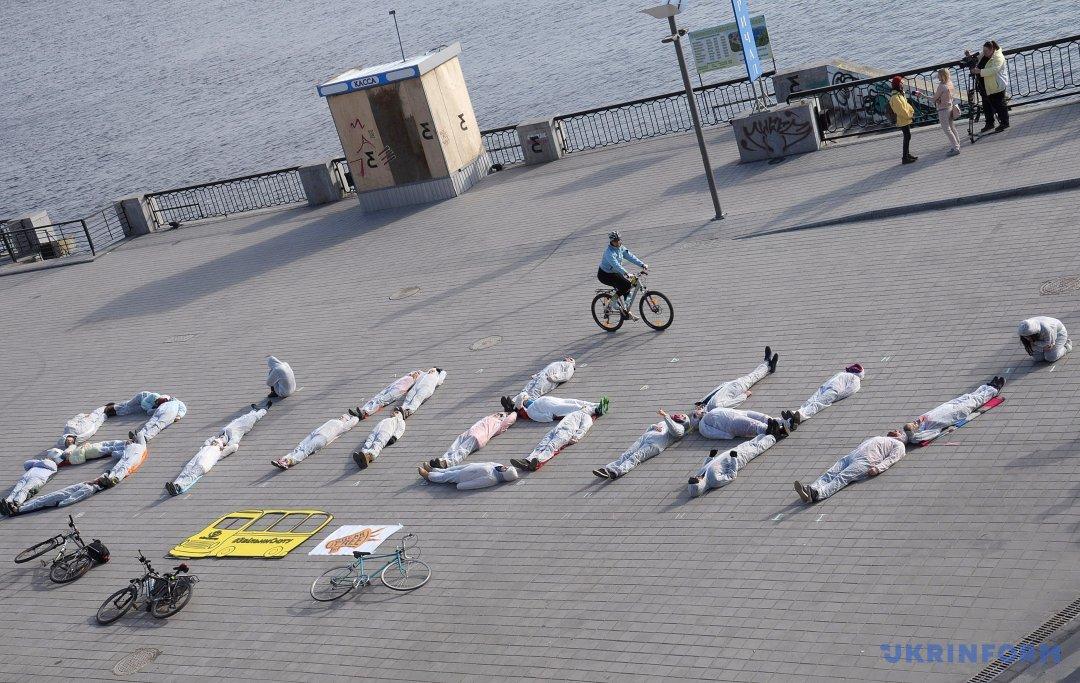 Активісти лежать на асфальті, формуючи слово