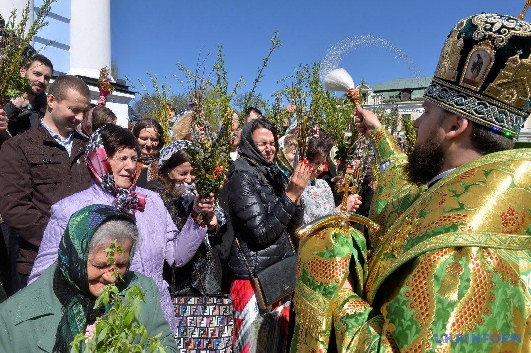 Священнослужитель окроплює вірян із вербовими гілками у руках під час святкування Вербної неділі біля Михайлівського собору, Київ, 9 квітня 2017 року. Фото: Володимир Тарасов