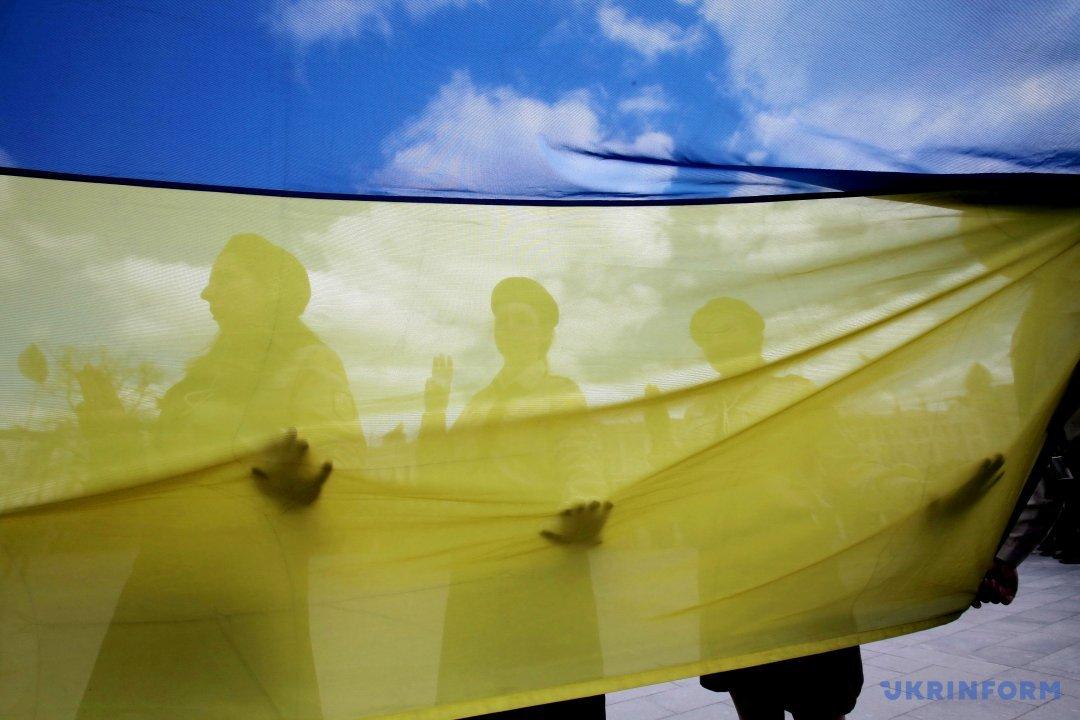 Люди тримають прапор України під час урочистих заходів з нагоди Дня першої пластової присяги на площі Конституції в Харкові, 8 квітня 2017 року. Фото:  В'ячеслав  Мадієвський