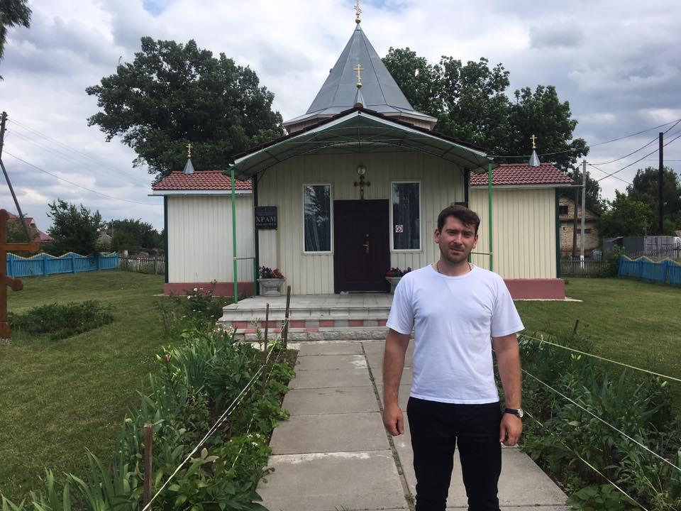 Отець Всеволод на фоні церкви Іоана Хрестителя