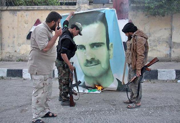 Сирійські повстанці спалюють портрет Асада / Getty Images