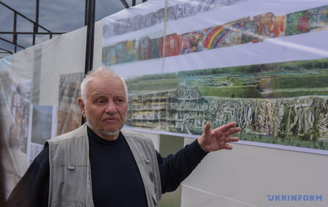 """Володимир Мельниченко, архітектор, один з двох авторів """"Стіни"""" показує на стенд з зображенням рельєфу"""