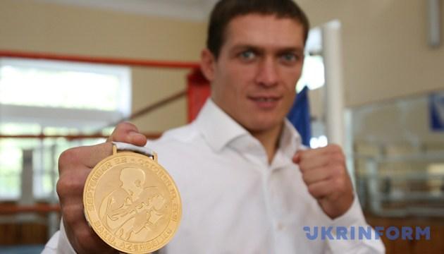 Боксер Олександр Усик демонструє свою золоту медаль під час прес-конференції. Сімферополь, 11 жовтня 2011 року. Фото: Укрінформ