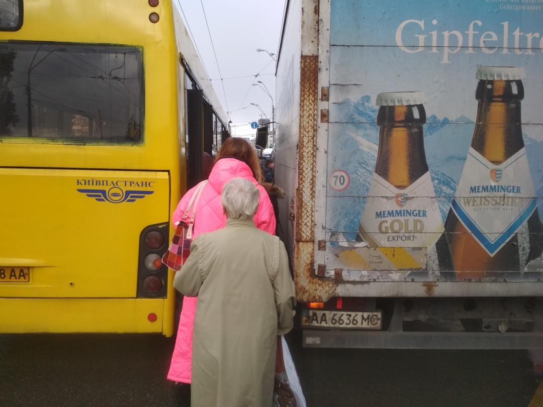 Через те, що вантажівка припаркувалася прямо на зупинці громадського транспорту - пасажири мусять протискатися вузьким