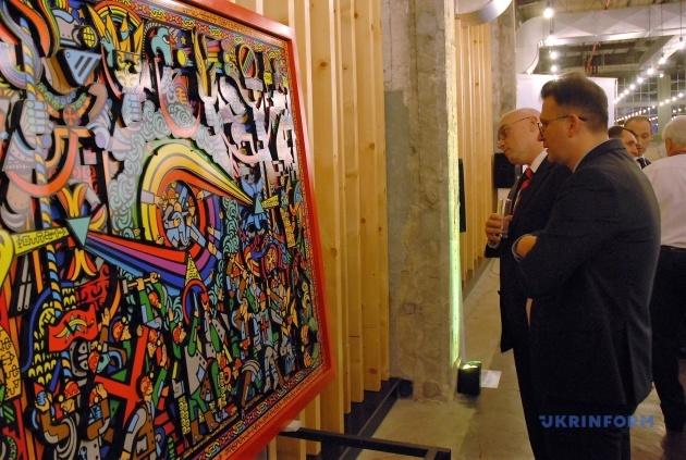 Відвідувачі експозиції розглядають картини