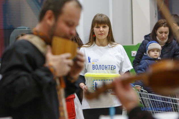 Волонтер Дарія Белейканич збирає кошти на користь військових під час концерту камерного оркестру Закарпаської філармонії під керівництвом Олени Короленко в ужгородському супермаркеті, 30.01.2015
