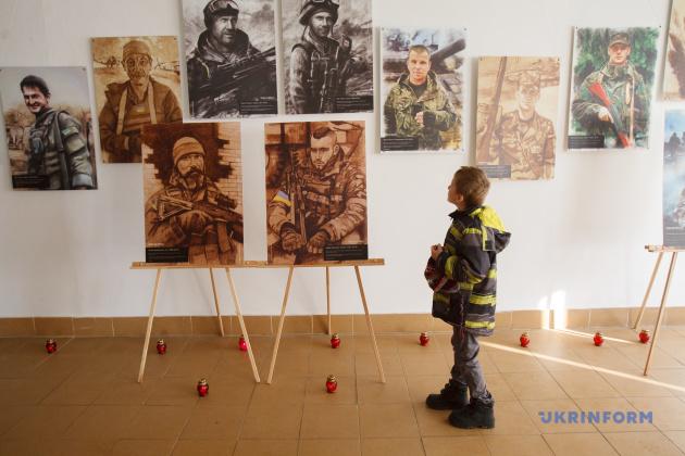 Хлопчик роздивляється портрети загиблих воїнів під  час виставки