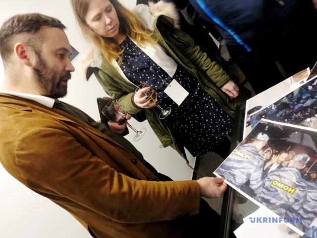 Илья Пономарев рассматривает фото, где его жестко задерживает ОМОН