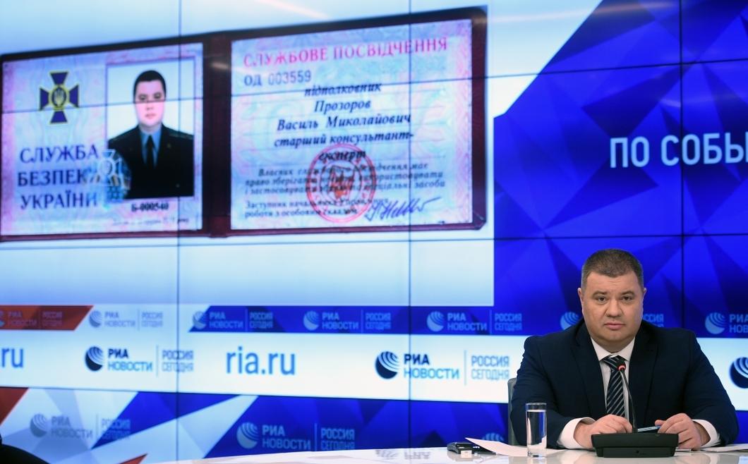 Прозоров демонстрирует журналистам фото своего удостоверения СБУ.