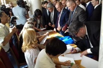 Депутаты в кулуарах подписывают присягу и получают удостоверения
