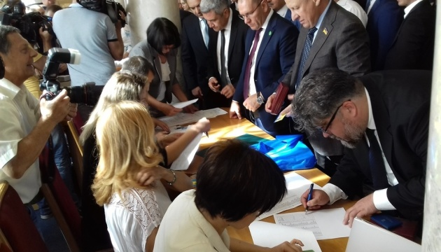 Депутати у кулуарах підписують присягу і отримують посвідчення