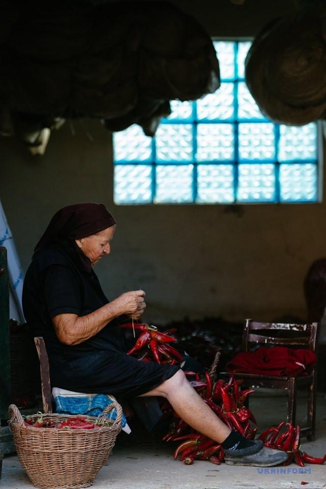 80-річна Моргіта нанизує перець на нитку для сушки