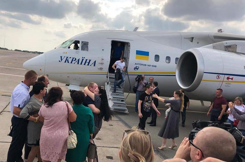 Михайло Власюк (у центрі), зліва Сергій Чуліба, на трапі літака Віктор Беспальченко
