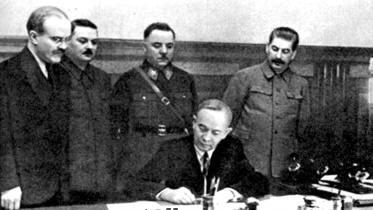 Отто Куусінен підписує