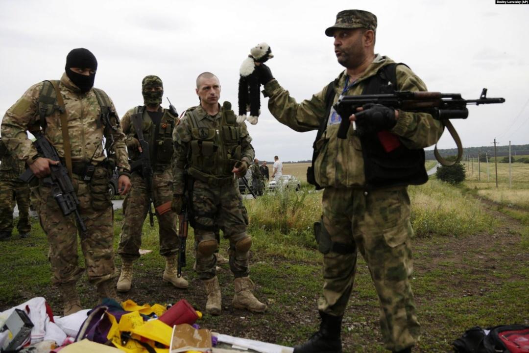 Бойовик російських гібридних сил тримає іграшку, виявлену на місці падіння уламків «Боїнга», збитого російською установкою «Бук», в результаті чого загинуло 298 людей, в тому числі 80 дітей. Донеччина, неподалік села Грабове, 19 липня 2014 року
