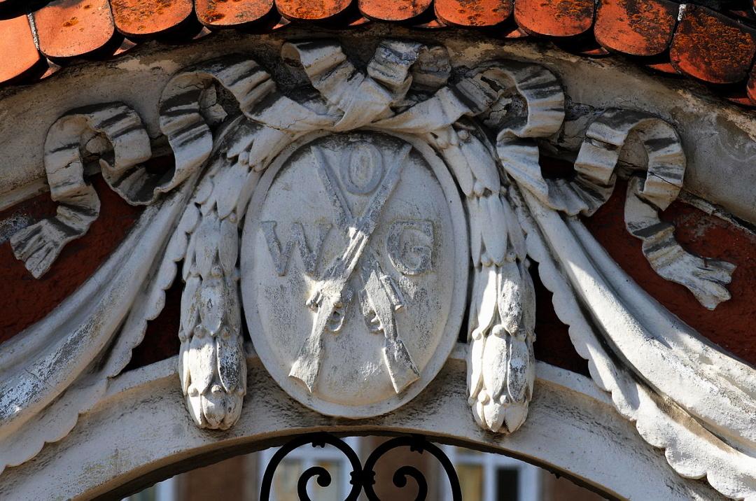 2-емблема Австрійського зброярського заводу на будинку №3 на площі Hessenplatz, у м.Штайрі