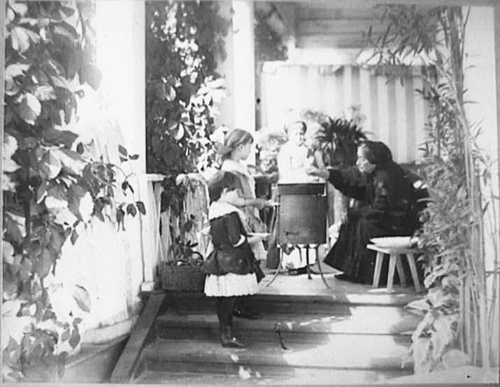 мати господаря Качанівки Людмила Володимирівна на веранді варить варення. Онуки готові зняти пробу, приблизно 1880 р.