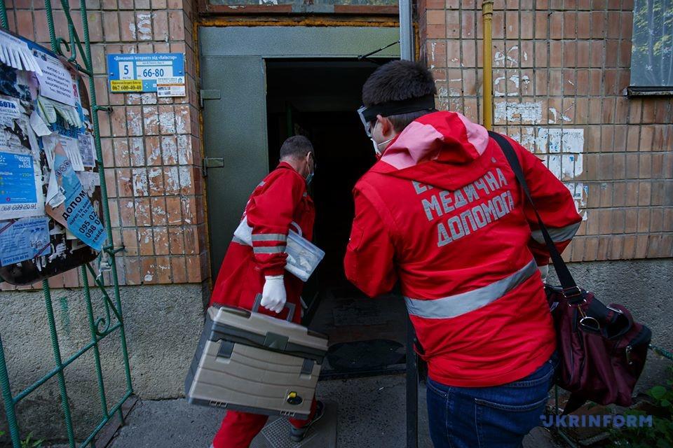 фельдшер Микола Головчак (ліворуч) та лікар Андрій Семедій забігають в під'їзд