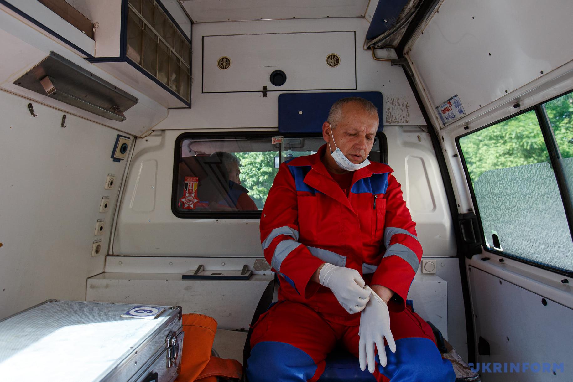 Фельдшер Іван Куцин одягає рукавички по дорозі на виклик