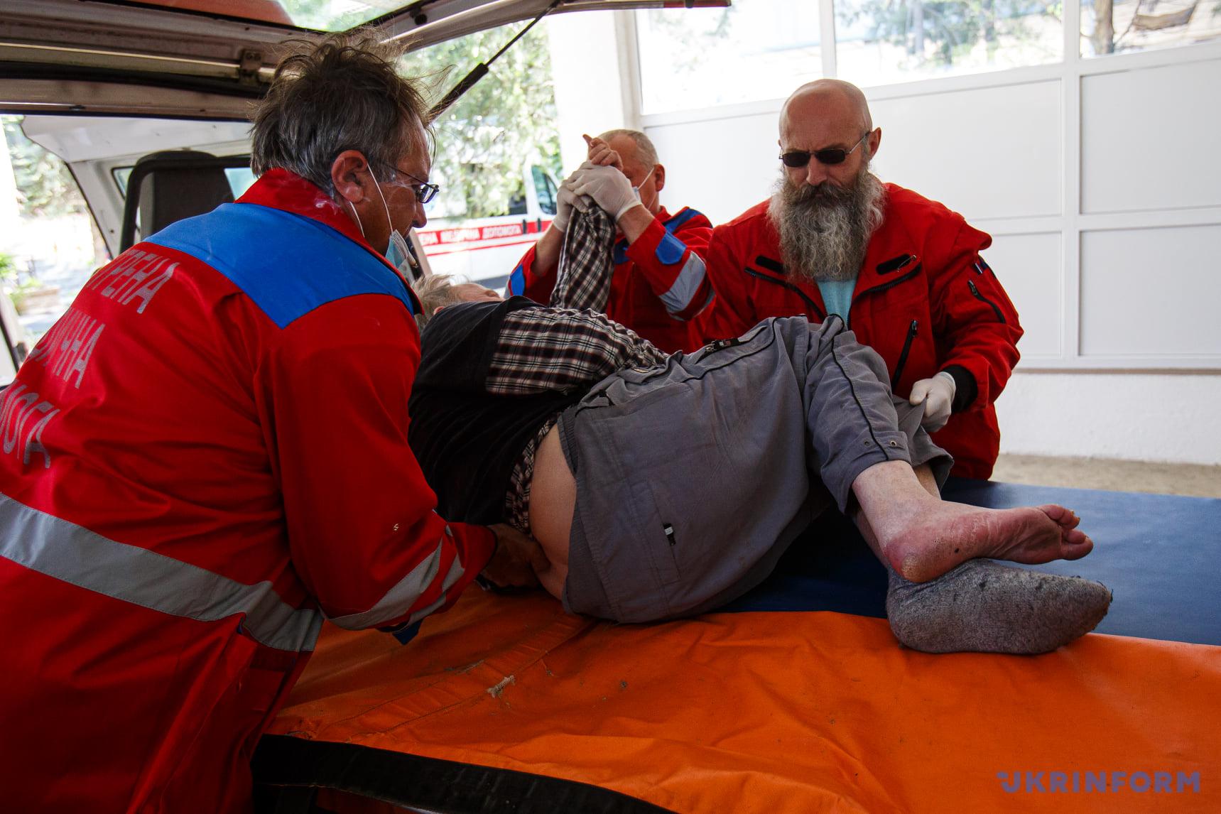 працівники екстреної медичної допомоги перекладають хворого з підозрою на перелом ноги на ноші в травмпункті