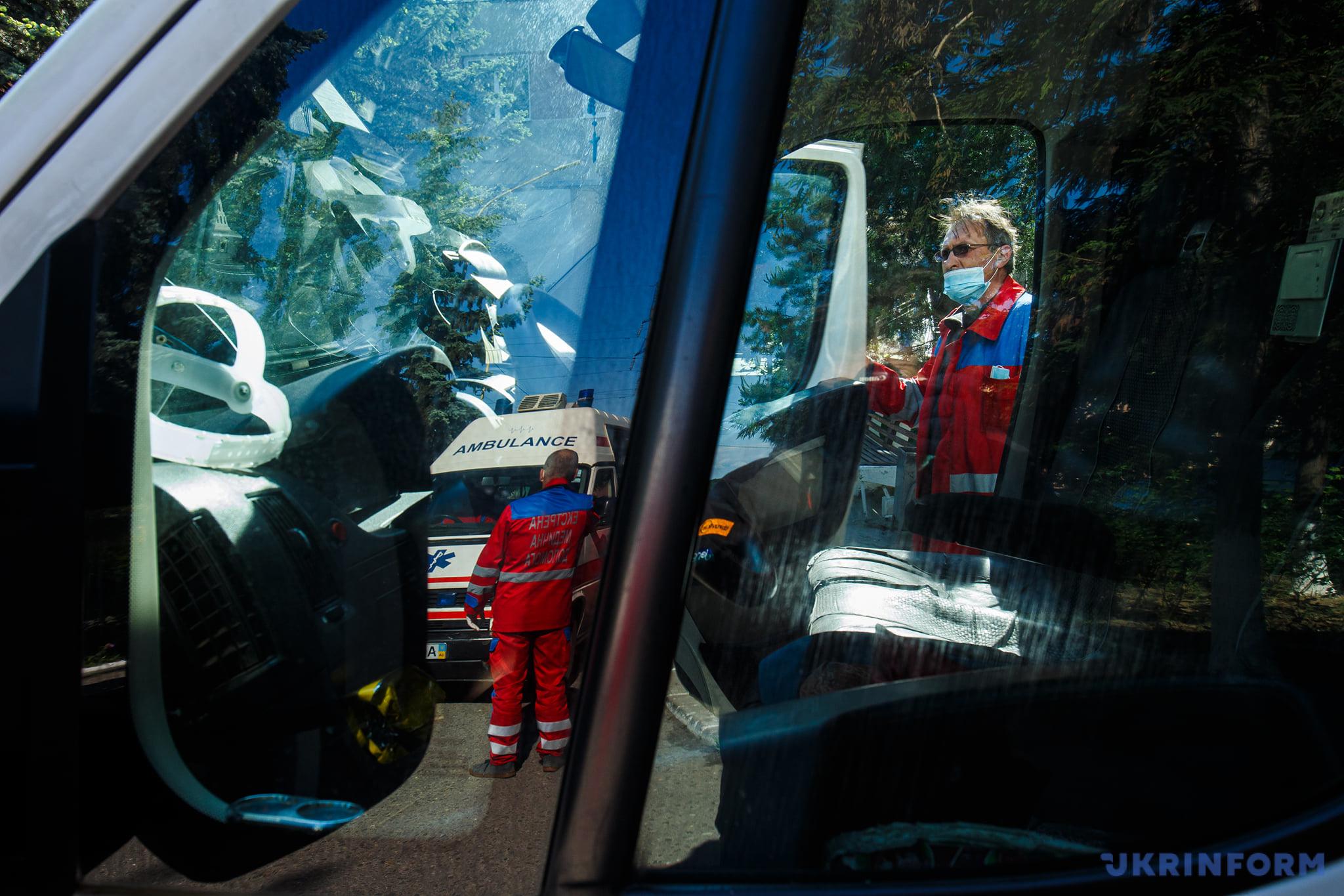Працівники екстреної медичної допомоги біля машин