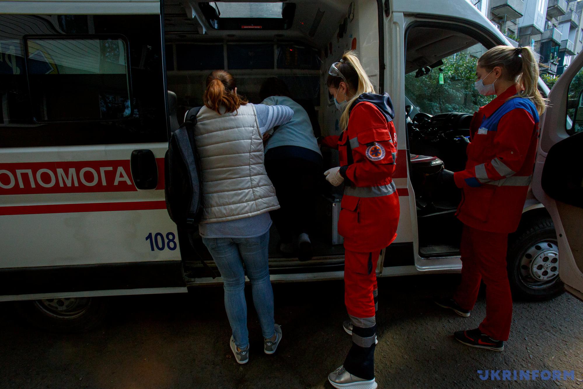 фельдшер Маріанна Мишанич допомагає хворій сісти в машину