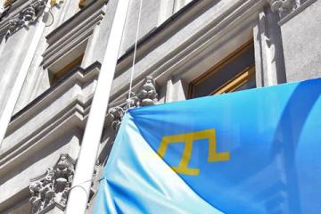 Kuleba, Chubarov y Dzhemílev izan la bandera tártara de Crimea cerca del Ministerio de Exteriores