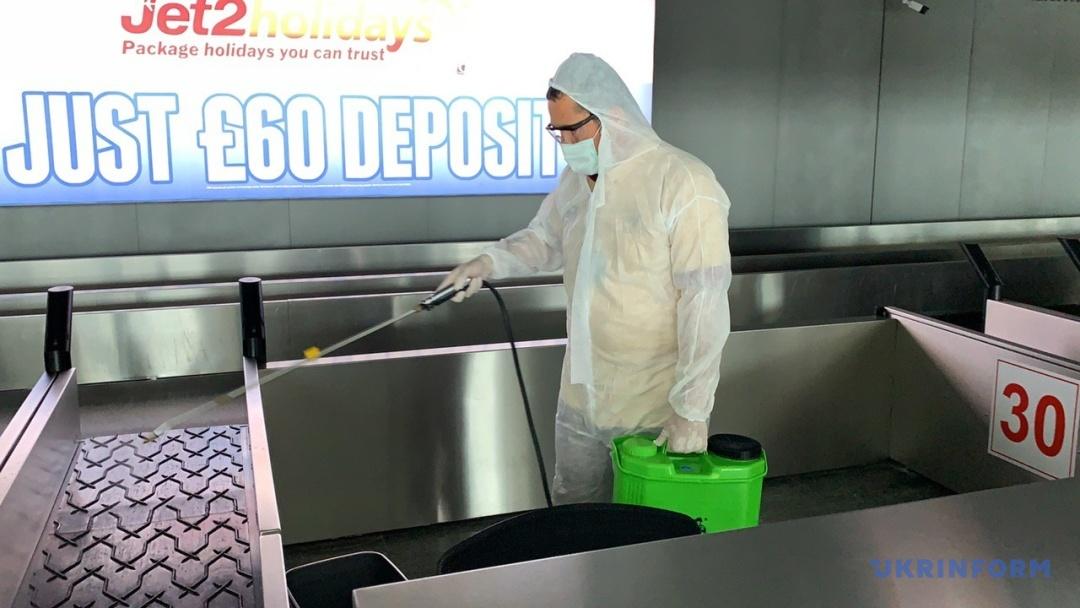 Дезінфекція багажної стрічки працівником аеропорту