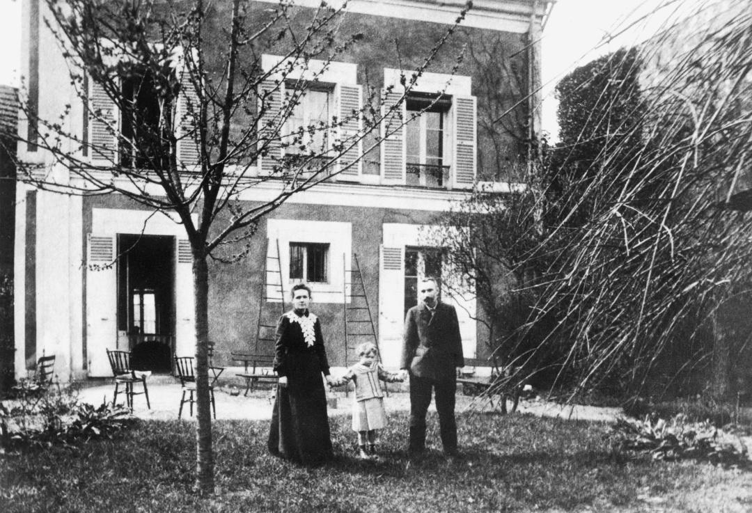 Марі та П'єр Кюрі позують із дочкою Іран біля родинного будинку