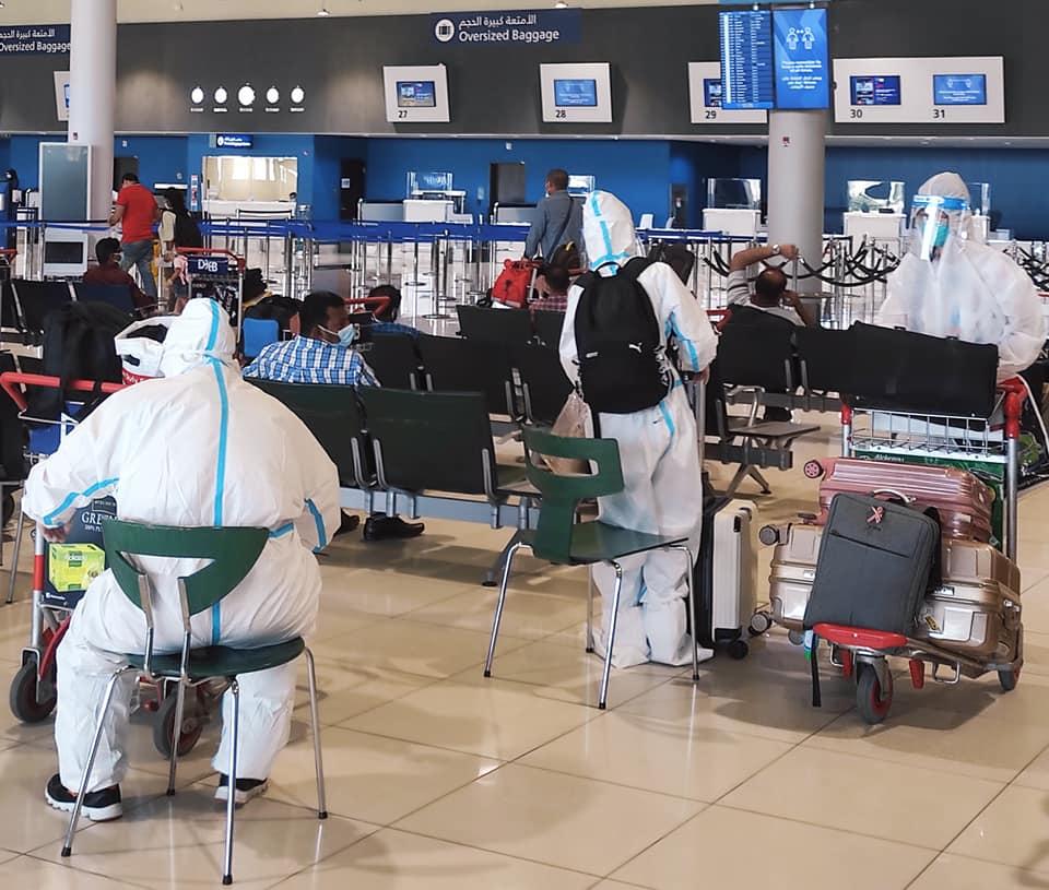 туристи з Оману чекають на літак у захисних костюмах
