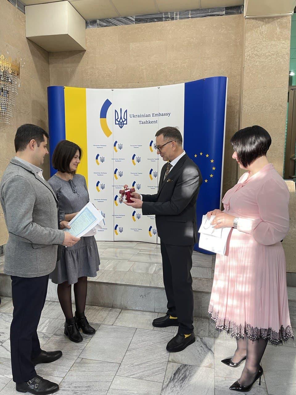 Посол України в Узбекистані Микола Дорошенко вручає ляльку-мотанку батькам новонародженої Яринки
