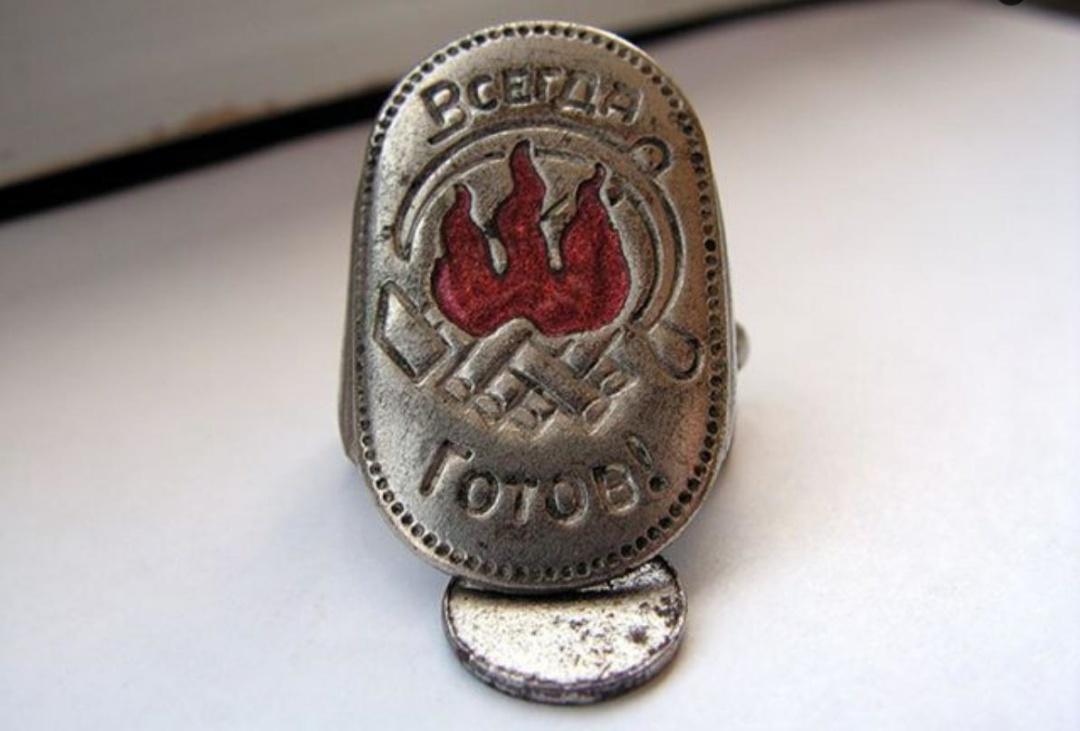 Затискач для піонерського галстука з уявною абревіатурою ТЗШ: «троцкистско-» (перевернуте багаття), «зиновьевская» (вогнище набік), «шайка» (вогнище в звичайному положенні)