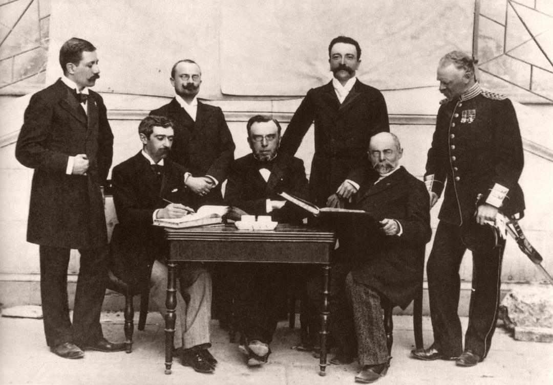 Перший склад МОК (зліва направо): 1. Доктор Віллібильд Гебхардт (Німеччина) 2. Барон П'єр де Кубертен (Франція) 3. Радник Іржі Гут-Ярковський (Чехія) 4. Деметріус Вікелас (Греція) 5. Ференц Кемені (Угорщина) 6. Генерал Олексій Бутовський (Україна, Росімперія) 7. Генерал Віктор Бальк (Швеція) (Афіни, 10 квітня 1896 року).